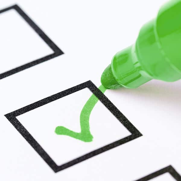 Green pen ticking a checklist box